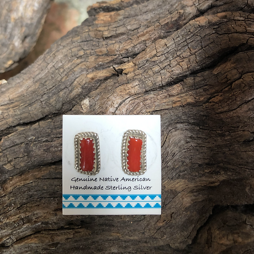 Small coral stud earrings set into sterling silver.