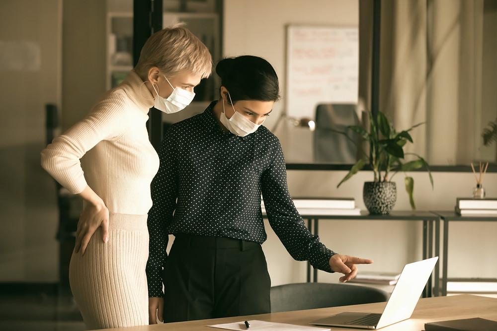 Digitalisering- to kvinner med munnbind som diskuterer over en laptop