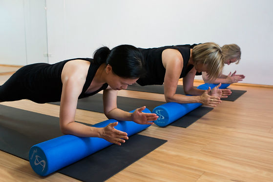 Women-in-dynamic-pilates-class-foam-roll