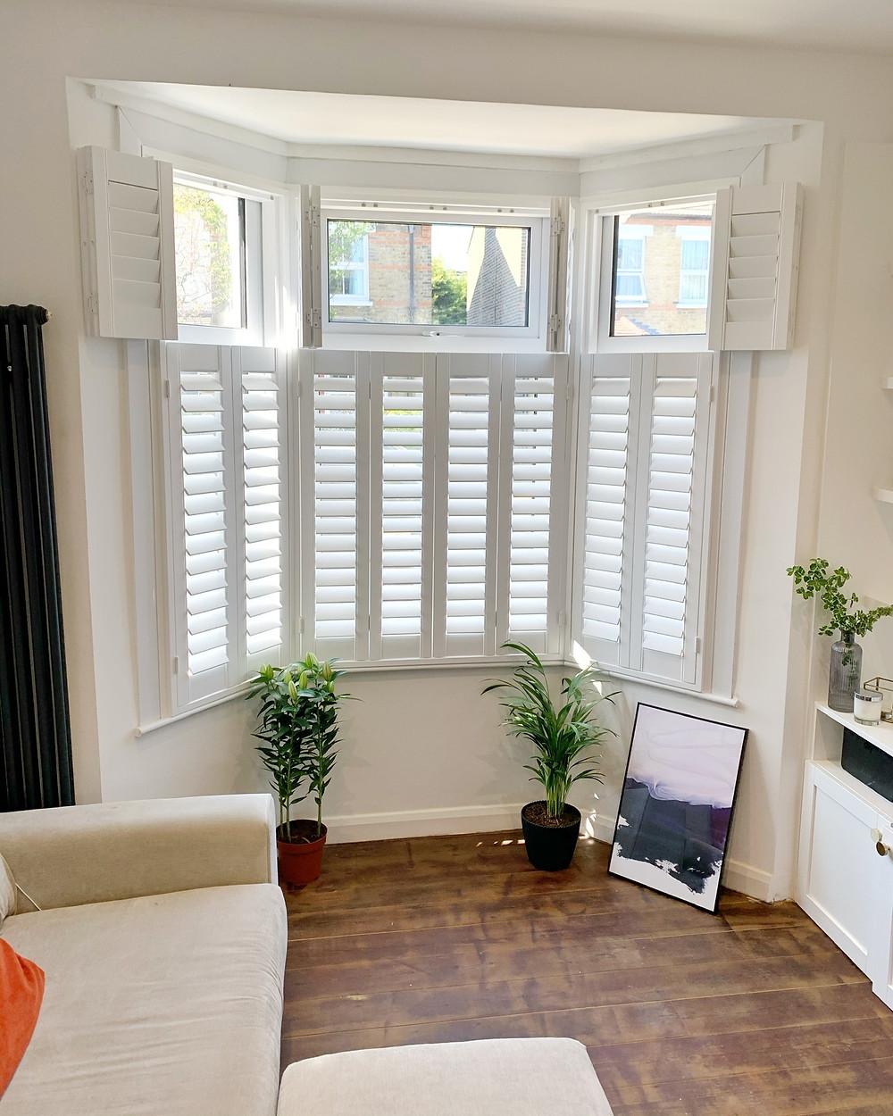 Tier on tier white wooden shutters