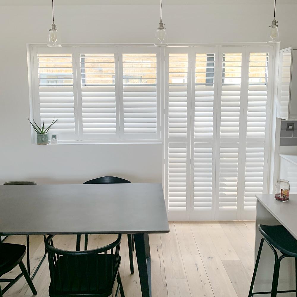 Full height white wooden window shutters