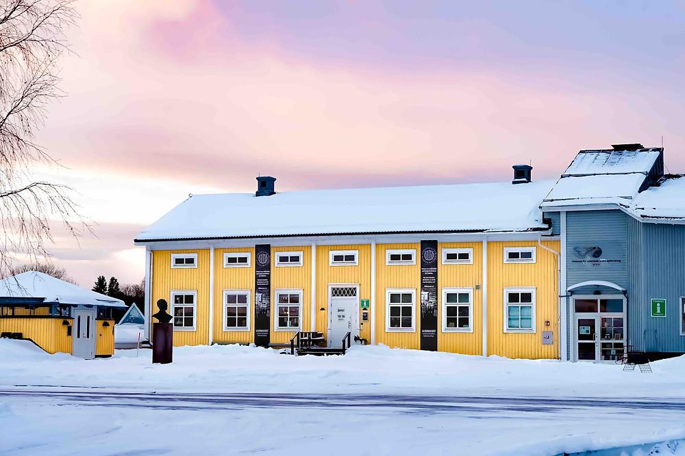 Silvermuseet i sin helhet utifrån, snö på marken och en himmel som skiner med glimmrande rosa/lila färger