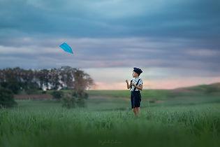menino de boina soltando pipa com céu az