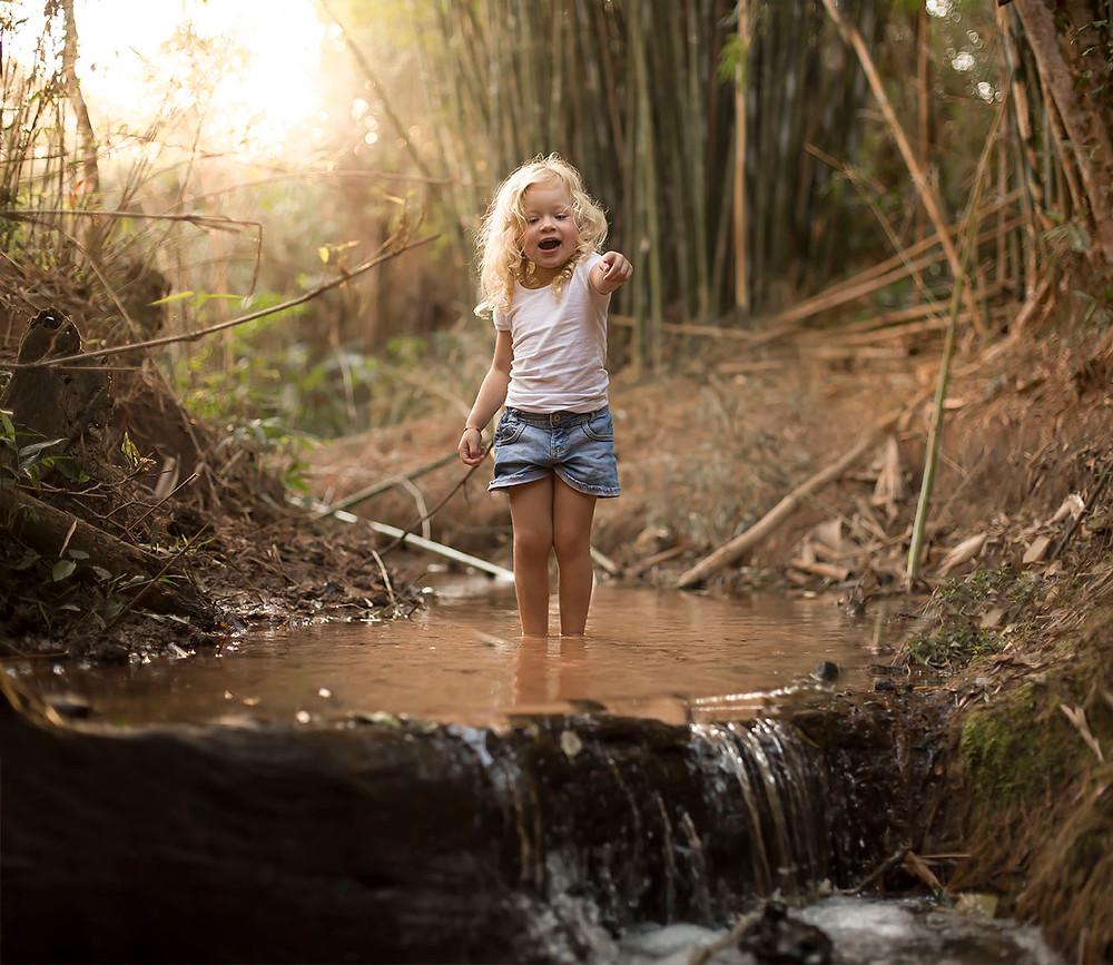 Ensaio infantil na natureza com riacho e pôr do sol