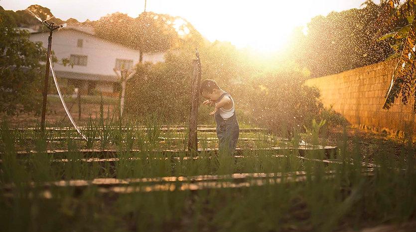 Menino brinca com água na horta