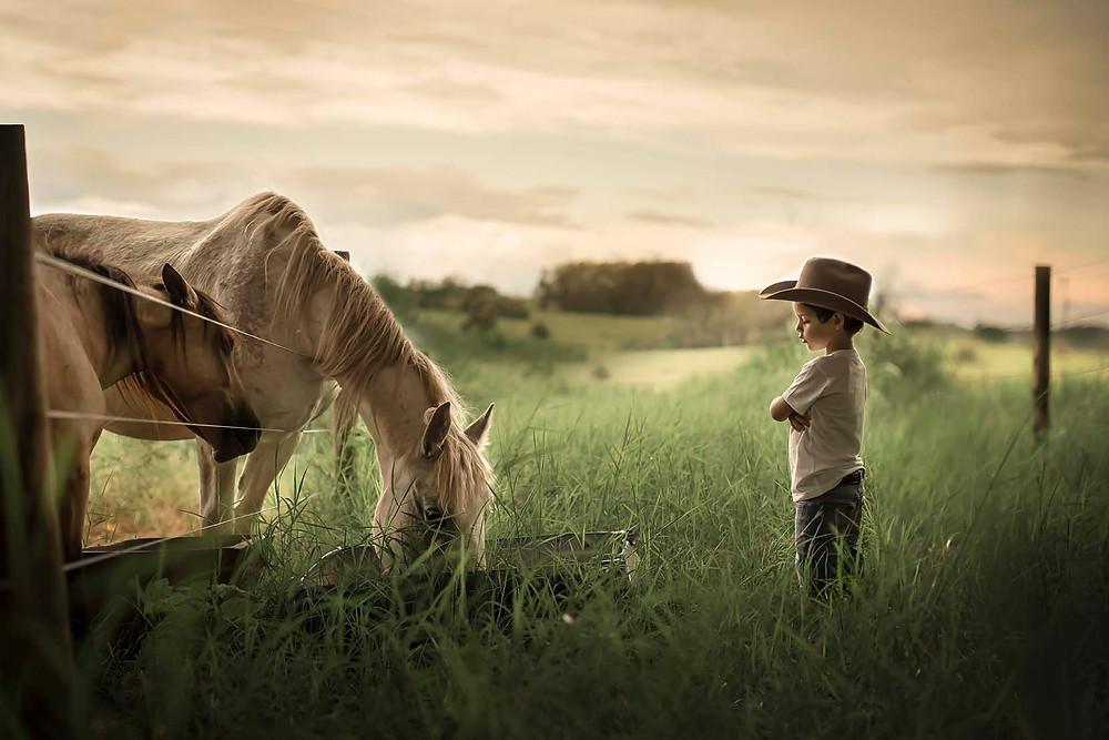 Retrato de menino com cavalos no sítio