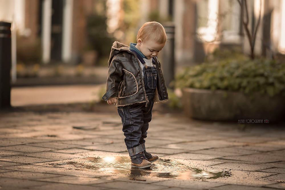 menino brincando na poça d´água após a chuva