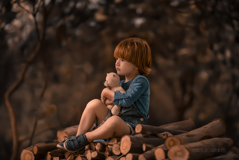 menino abraçado em ursinho de pelúcia no parque