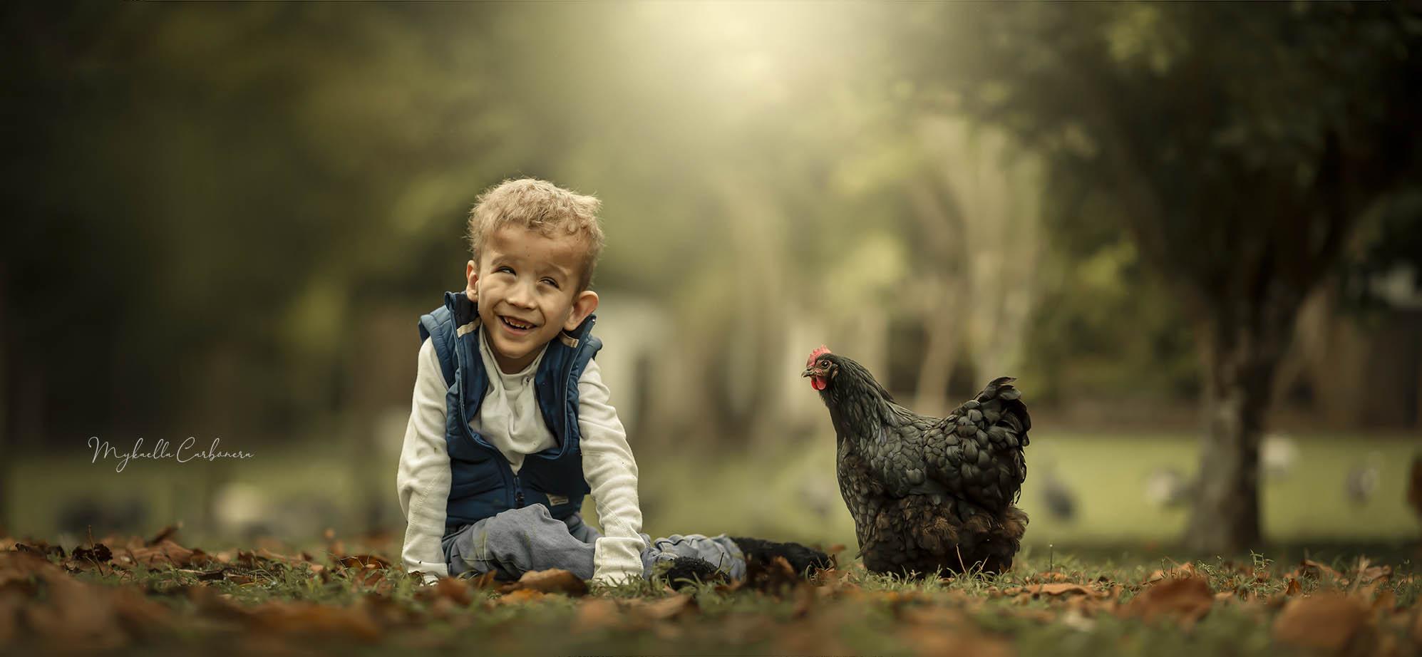 menino brincando com galinha preta