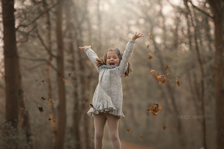 menina feliz jogando folhas para o alto.