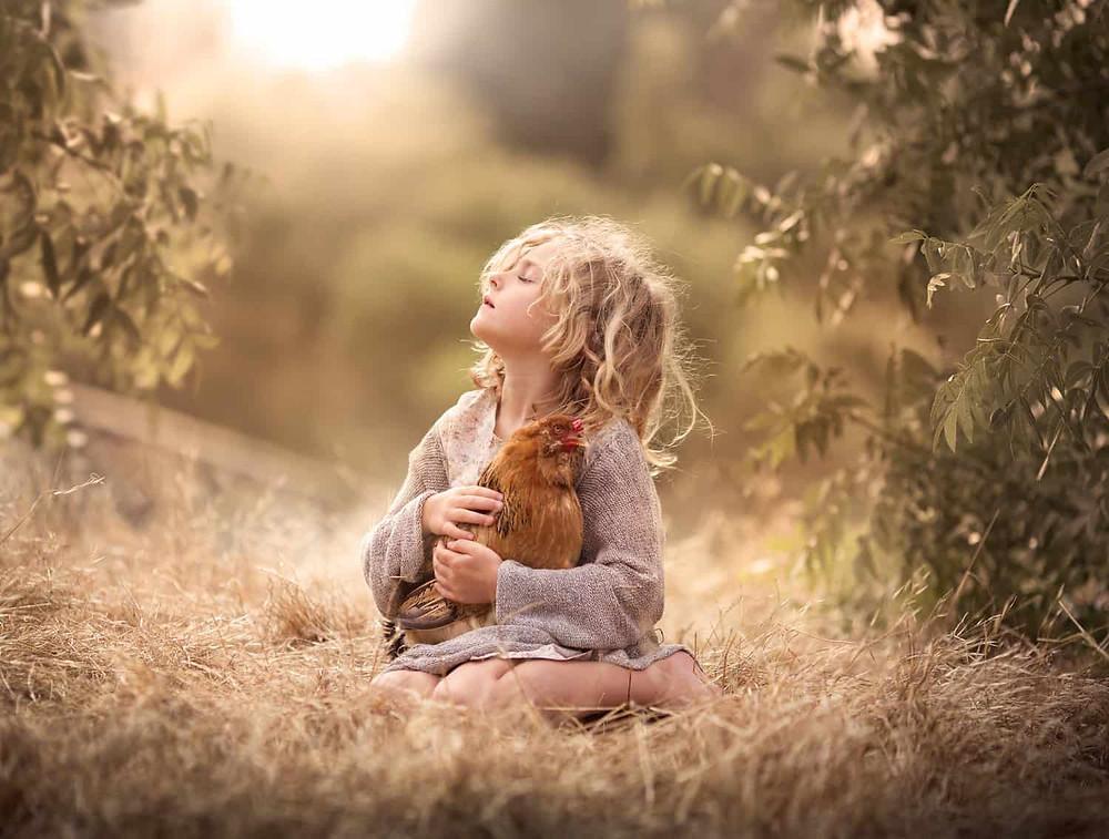 criança loira segurando galinha na natureza