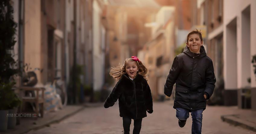 Irmãos correndo no meio da rua