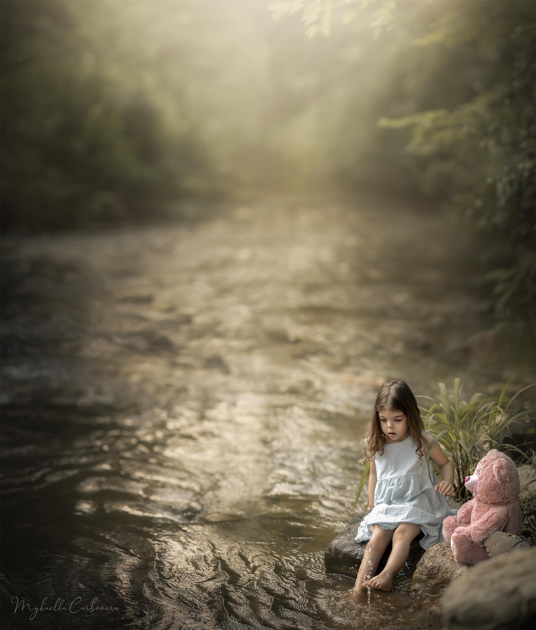 Criança com ursinho rosa no rio