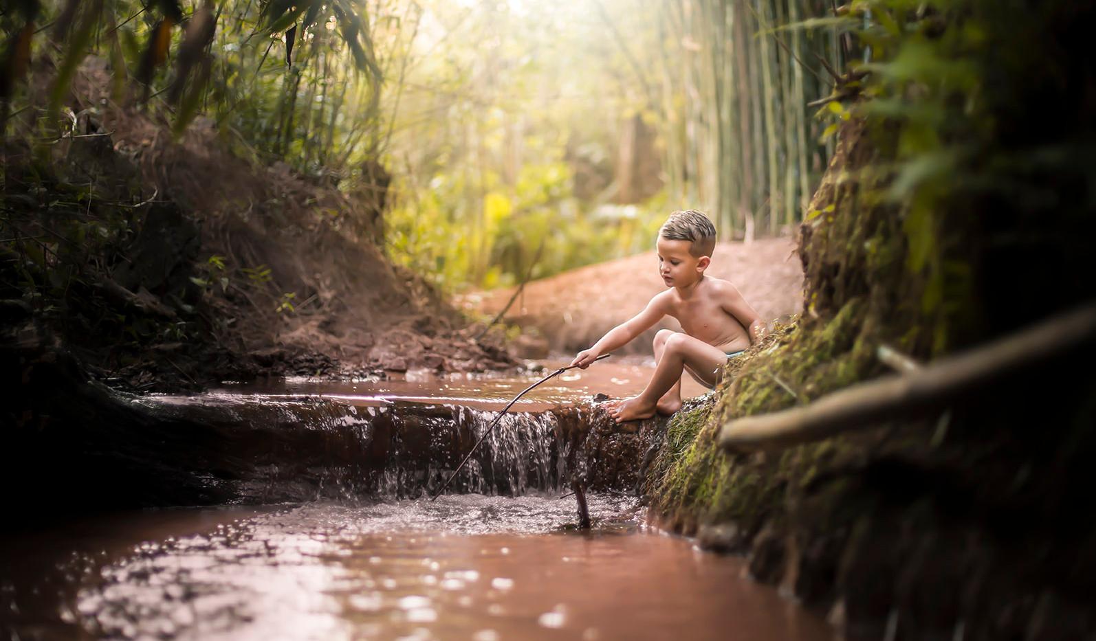 Menino brincando de pescar no rio