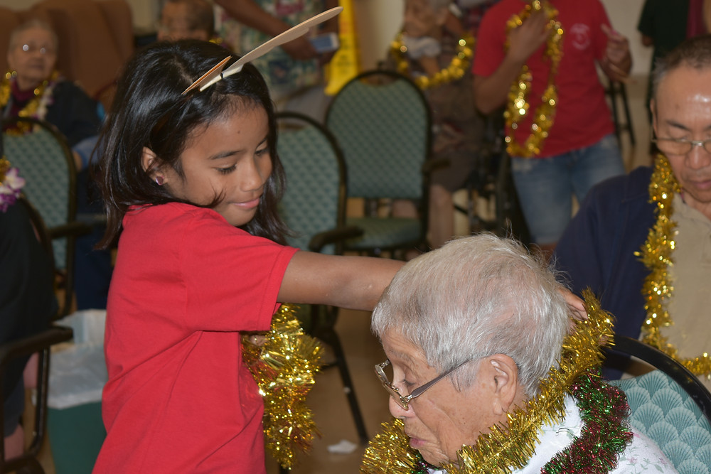 A Common Grace student from Pālolo Elementary puts a festive lei on an elder at Pālolo Chinese Home, where the keiki went Christmas caroling.
