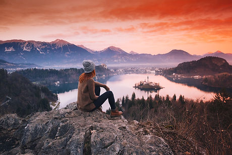 Travel Slovenia, Europe. Woman looking on Bled Lake with Island, Castle and Alps Mountain on backgro