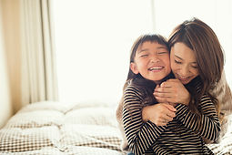 Mom hugging child from behind.