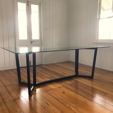 custom made dining table with a solid frame and glass top for in a Brisbane residence