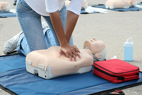 Female instructor showing CPR on trainin