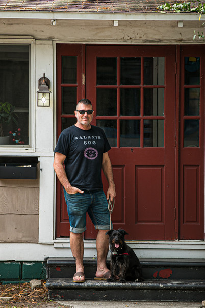 """""""I was caught a bit off guard when I got the text, asking if Sandra could take a portrait of me on my front stoop. I was just coming back from a dog walk… one of my rare excursions from home during this weirdest of times. There I was, not exactly sure when I had last bathed, with my fresh self-inflicted haircut, in a pair of jorts… not really giving a damn about what anyone thought about how I looked… and then, out of the blue, I was having my picture taken. I guess this scenario about sums up our situation, that we were all caught off guard."""" - Todd Bates - Artist"""