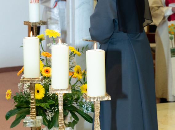 An der Osterkerze entzündet die Schwester ihre Professkerze