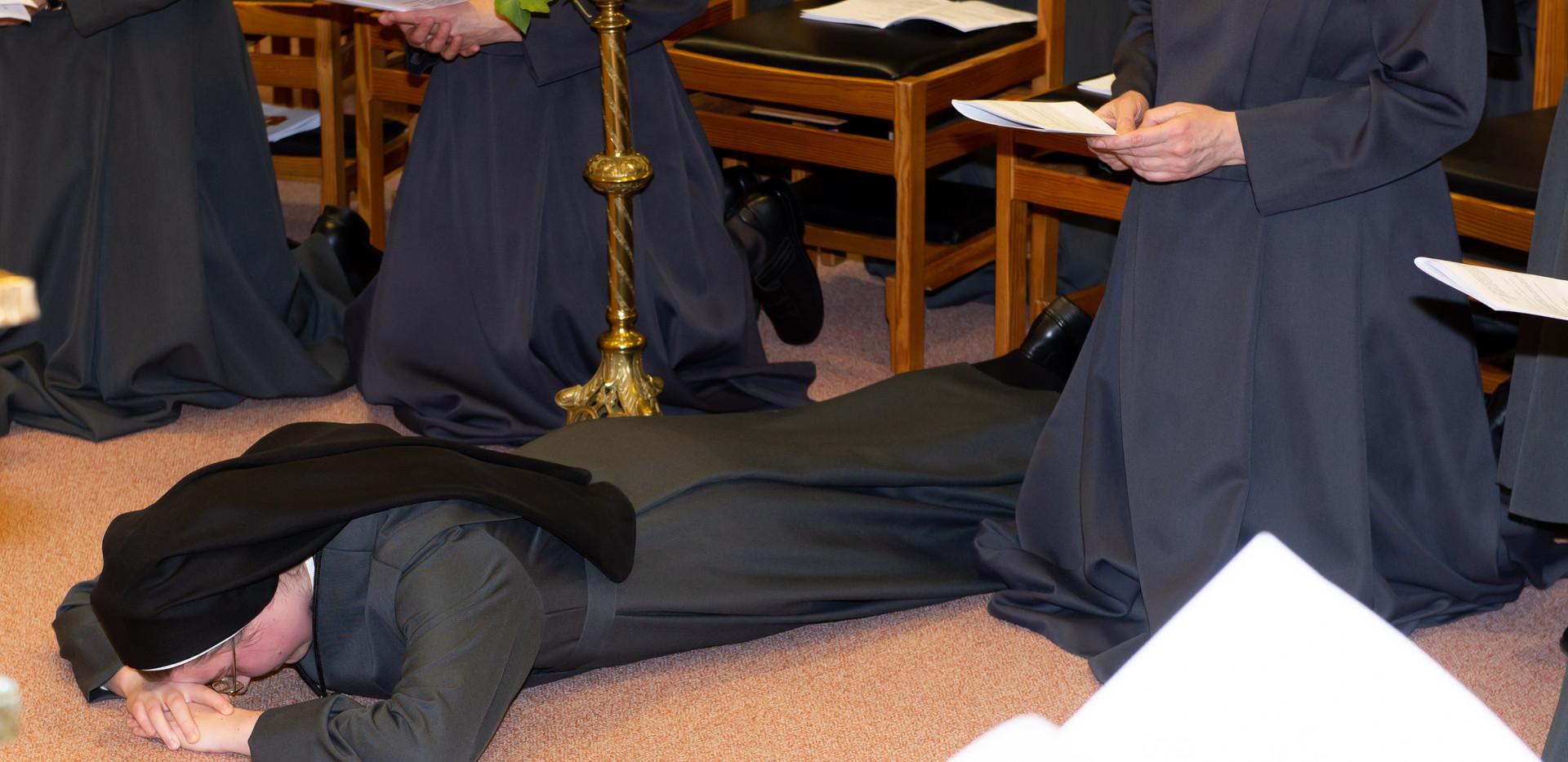 Als Ausgruck ihrer Ganzhingabe liegt die Schwester auf dem Boden, während die Fürsprache der Heiligen angerufen wird