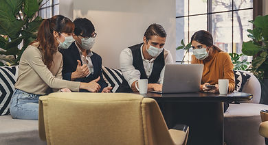 four people in an office environment, wearing face masks and looking at a laptop