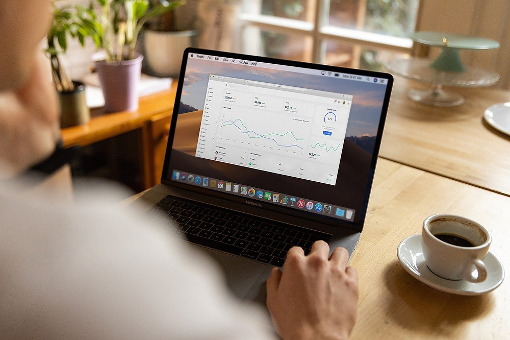 Image of man remote working from home with laptop on dining table