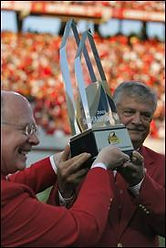 Lee Fowler and Chancellor Jim Oblinger present the Meineke Car Care Bowl Trophy to the fans.