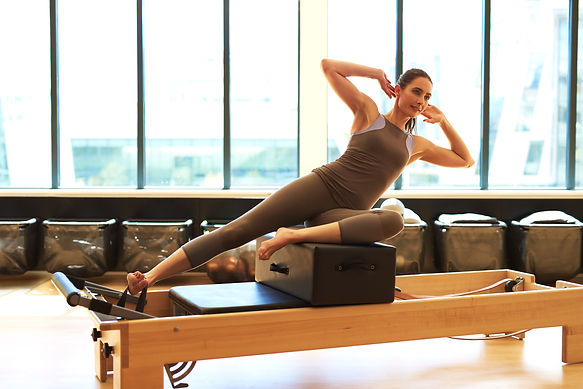 brunette-woman-practicing-pilates-in-stu