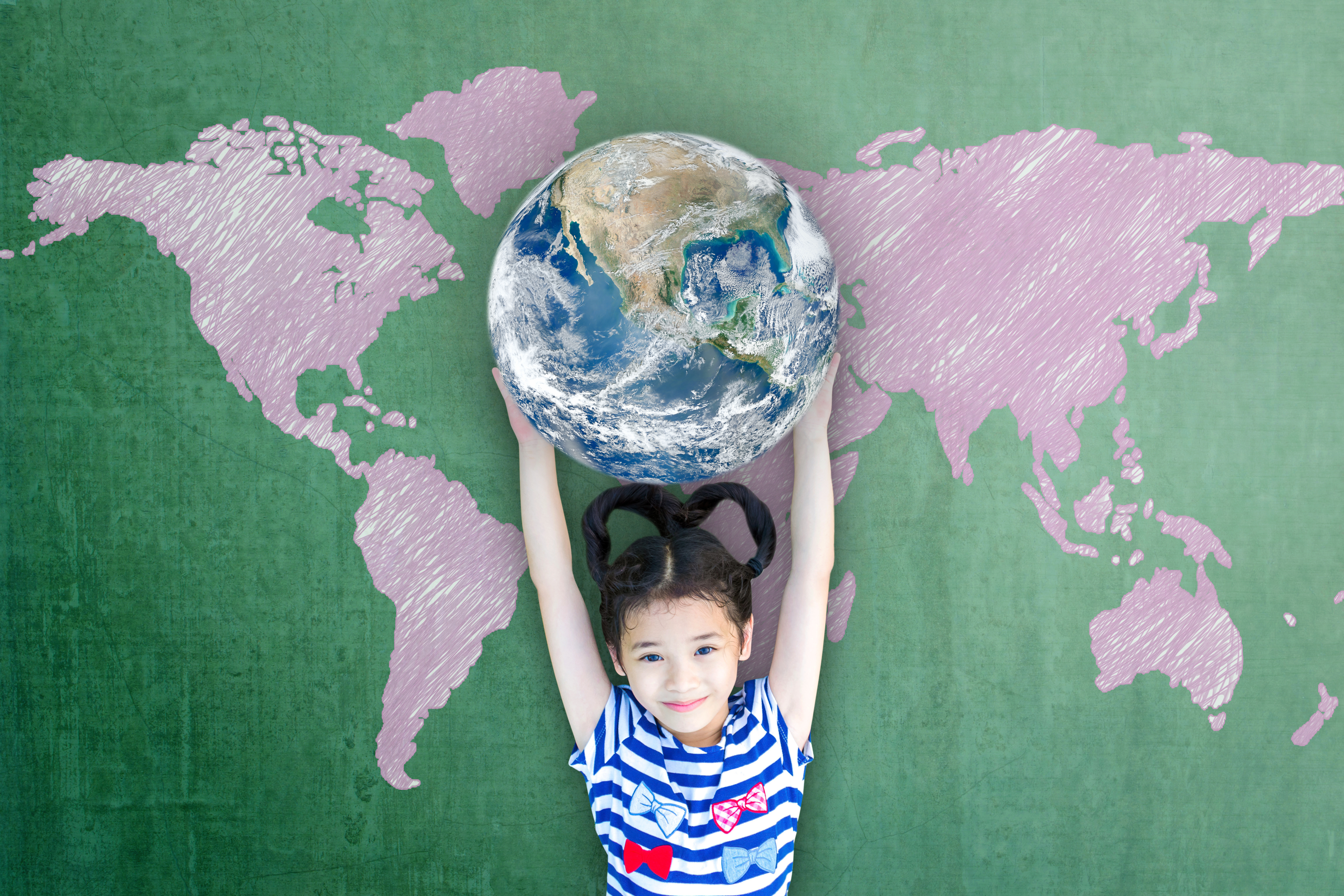 Global education and world literacy day concept with Asian girl kid student raising earth on chalkbo