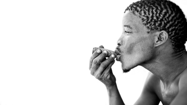A black and white portfolio image of a San tribesman smoking a pipe by Toronto based commercial photographer BEN HEMMINGS MEDIA