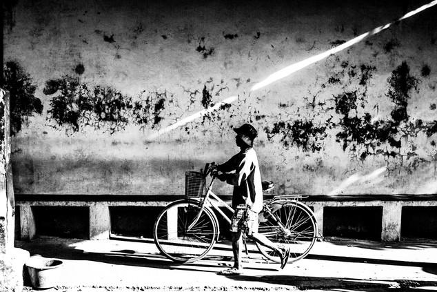 A burmese man pushes a bike through a train station