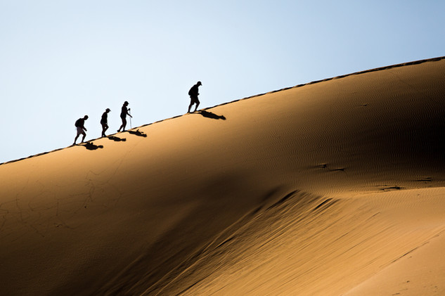 A group of tourists hike up the dunes at Sossusvlei, Namibia