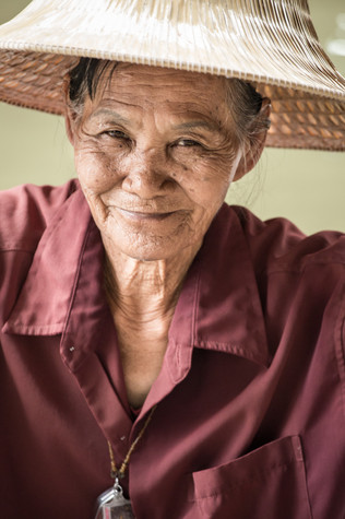 A portfolio image of a Thai river vendor smiling at the camera by Toronto based commercial photographer BEN HEMMINGS MEDIA