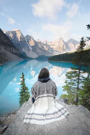 A woman sits on a rock at Moraine Lake in Banff national Park and watches the sun on the mountains in the distance