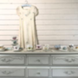 vintage dresser with wedding dress and teacups