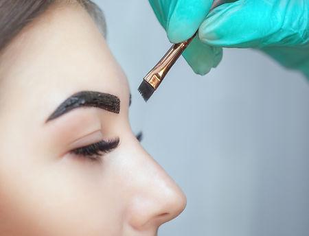 makeup artist applies paint henna on eye