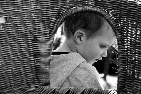 A wicker window into a boy's world as he plays in the garden during a candid portraiture session