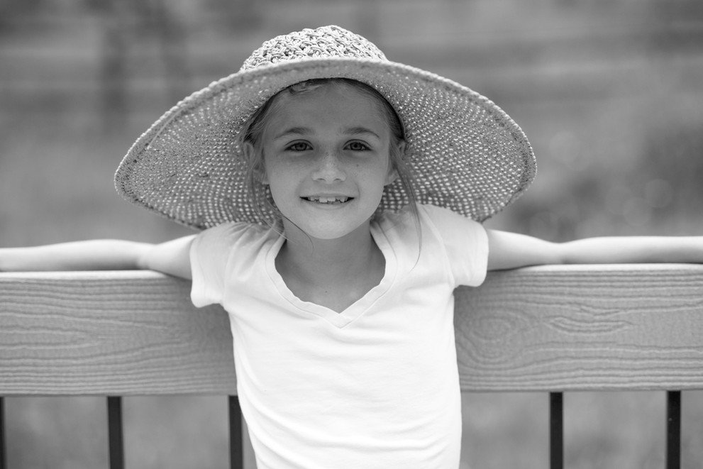 Smile under a sun hat during a candid portraiture session