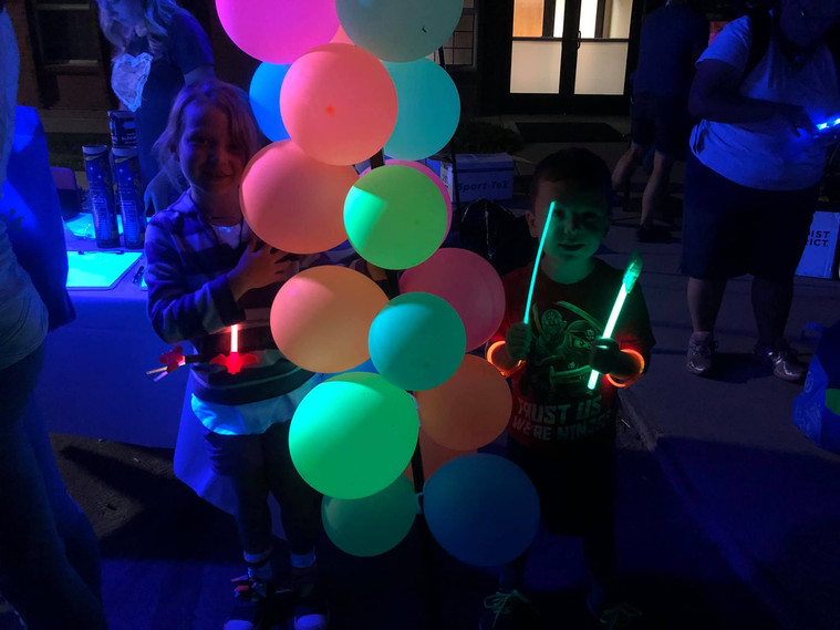 2 kids by lite up tent cool pic.jpg