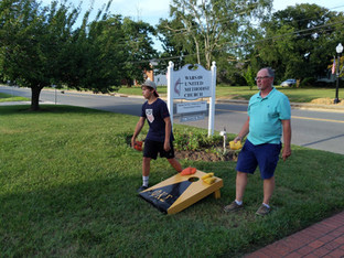 Members enjoying corn hole out on the front lawn of the church.