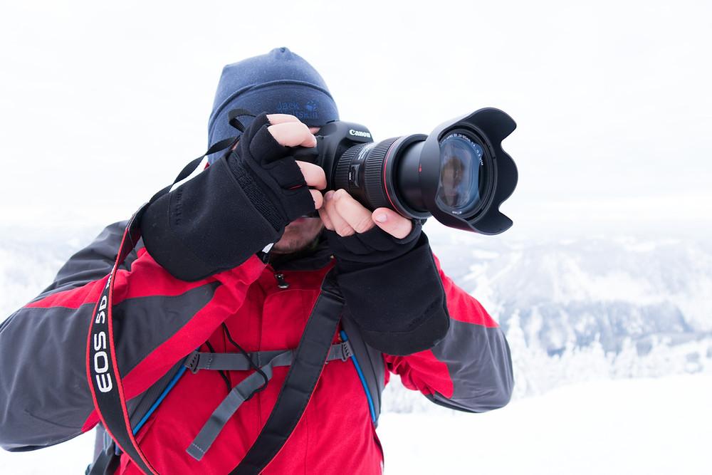 Fotograf Gerald Lechner mit Kamera im Winter mit Fotohandschuhen