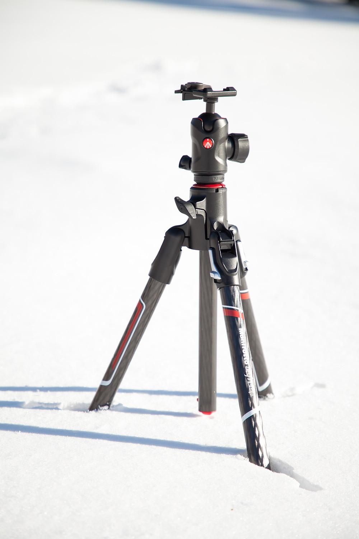 Ein im Schnee eingesunkenes Dreibeinstativ von Manfrotto Befree GT XPRO Carbon