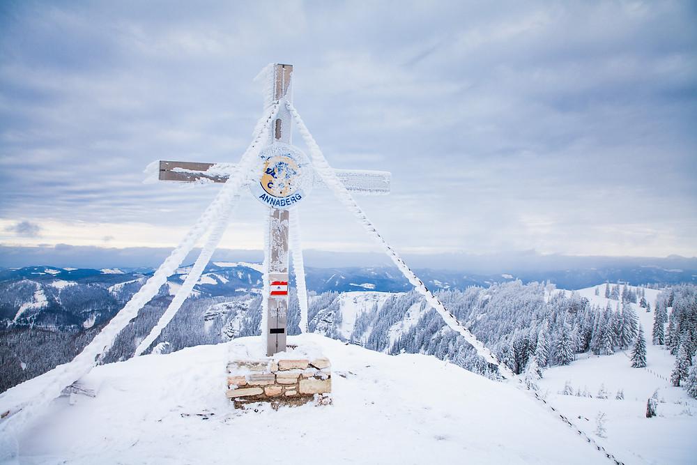 Gipfelkreuz des Annaberges verschneit und zugefroren im Winter vor dem Voralpenland