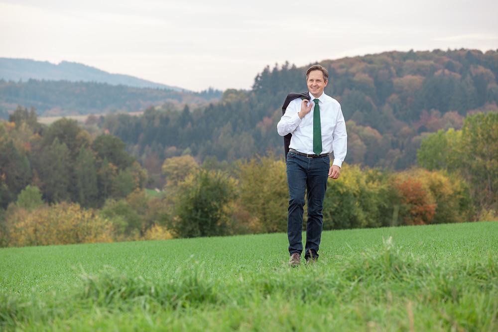 LKNÖ Präsident Johannes Schmuckenschlager gehend in Wiese vor Wald