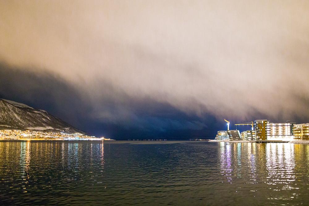 Schneesturm über Tromsö im Hafen mit Blick aufs Meer im Winter