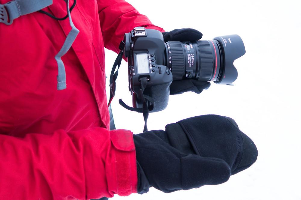 Fotograf Gerald Lechner mit Canon DSLR Fotokamera im Winter mit Fotohandschuhen