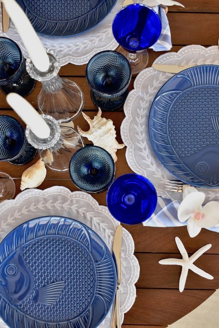 Linda composição de mesa posta nas cores azul e branco com detalhes de praia