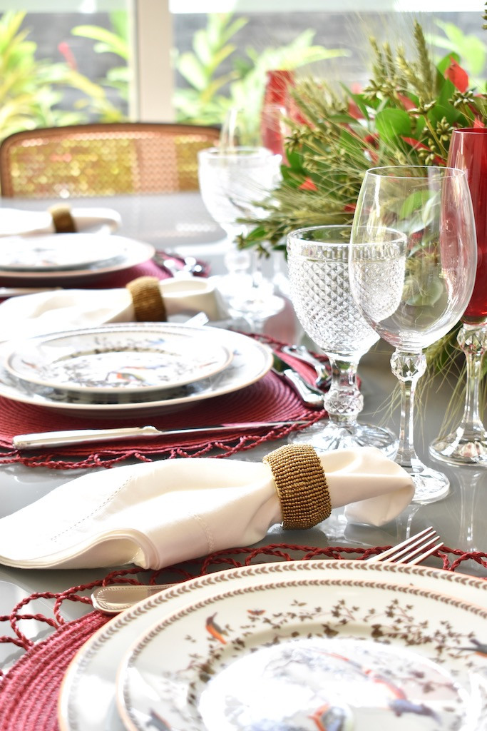 Guardanapo de algodão branco com porta guardanapo dourado na mesa posta.